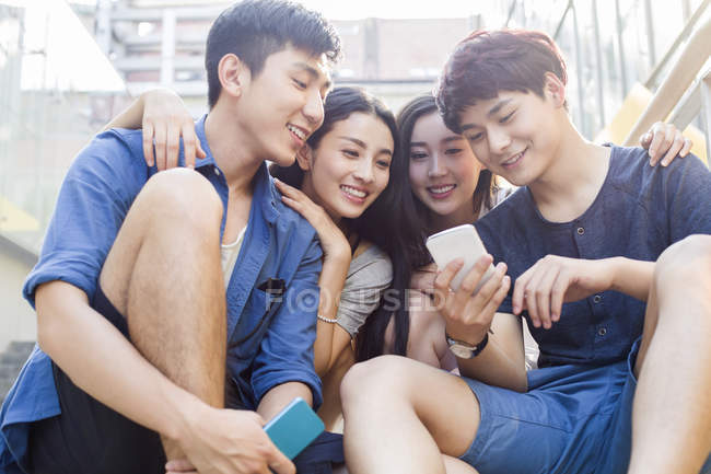 Chinesische Freunde schauen gemeinsam auf Smartphone-Bildschirm — Stockfoto