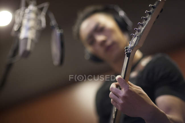 Chinese man playing guitar in recording studio — Stock Photo