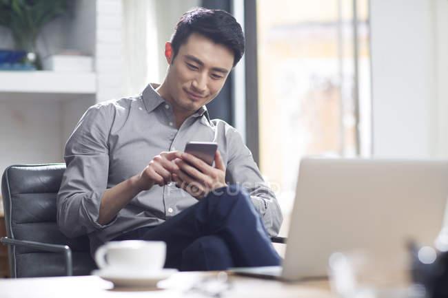 Uomo asiatico utilizzando smartphone in ufficio — Foto stock