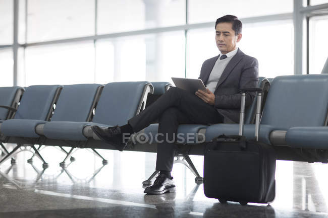 Asian man waiting in airport and using digital tablet — Stock Photo