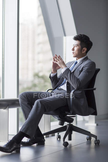 Chinese businessman sitting in chait and looking through window — Stock Photo