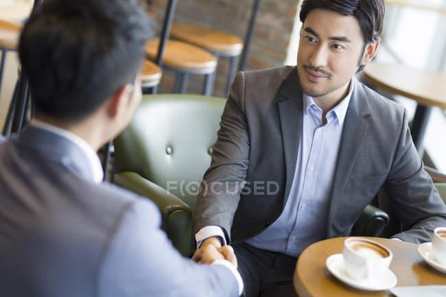 Китайський бізнесменів, потискує руку в кафе — стокове фото