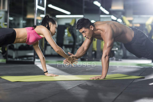 Chinese couple doing plank position at gym together — Stock Photo