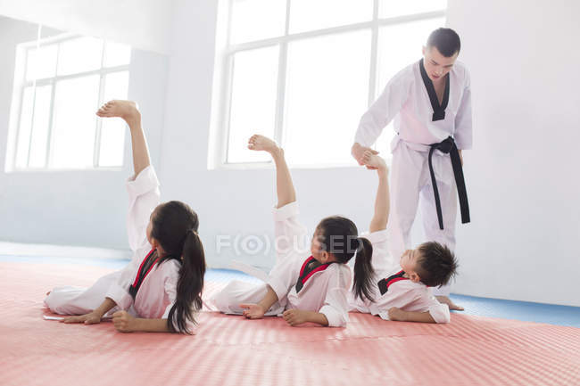 Chinese children exercising with Taekwondo instructor — Stock Photo