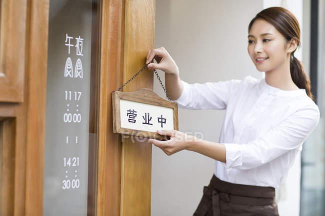 Camarera china colgando cartel abierto en la puerta del restaurante - foto de stock