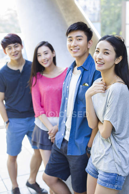 Chinese friends standing on street and looking in camera — Stock Photo