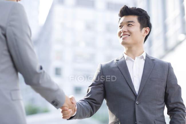 Chinesische Geschäftsleute beim Händeschütteln auf der Straße — Stockfoto