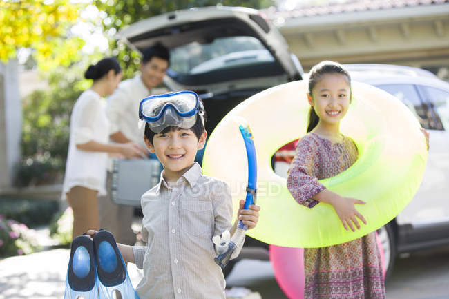 Chinese siblings with water sports equipment posing in front of car and parents — Stock Photo