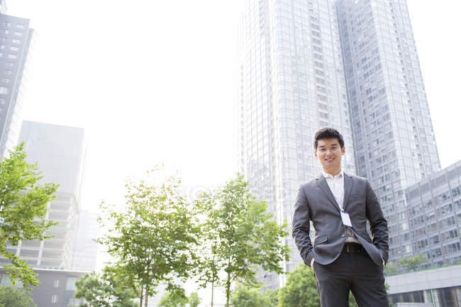 Chinese businessman standing on street and looking in camera — Stock Photo