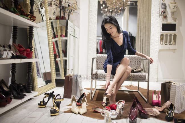 Donna cinese che prova le scarpe in negozio — Foto stock