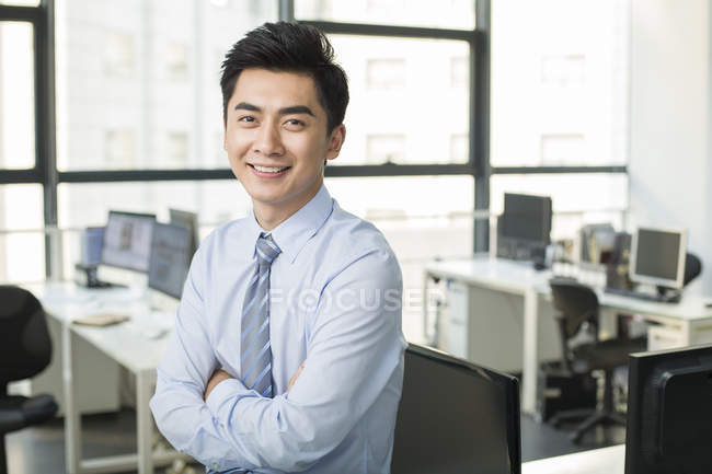 Uomo d'affari cinese con le braccia incrociate sorridente in ufficio — Foto stock