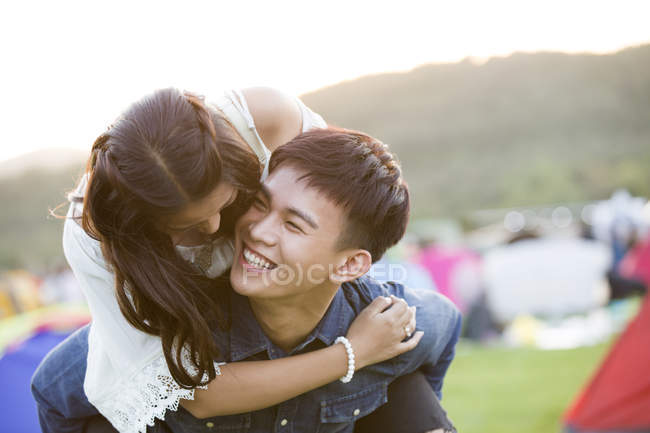 Happy chinese couple riding piggyback at festival camping — Stock Photo
