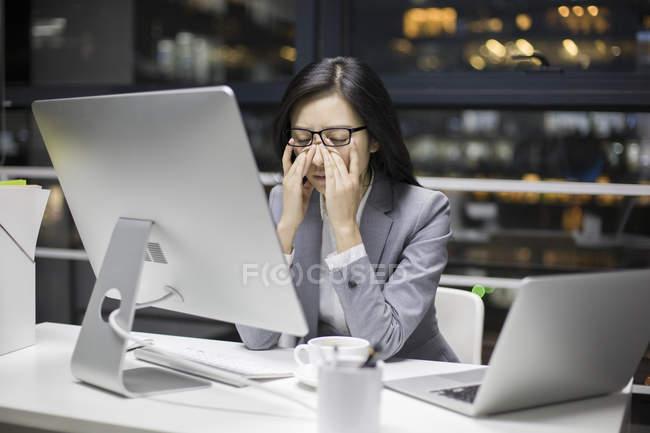 Empresária chinesa cansada, trabalhando até tarde no escritório — Fotografia de Stock