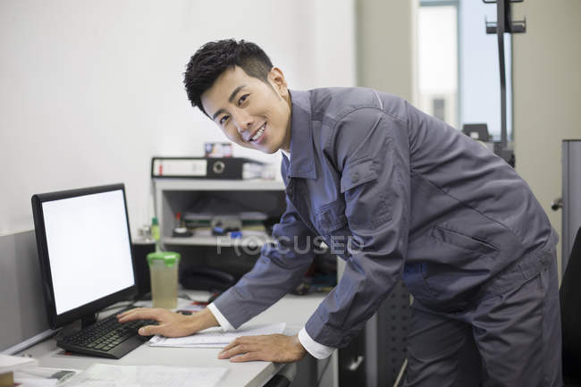 Chinese auto mechanic working with computer — Stock Photo