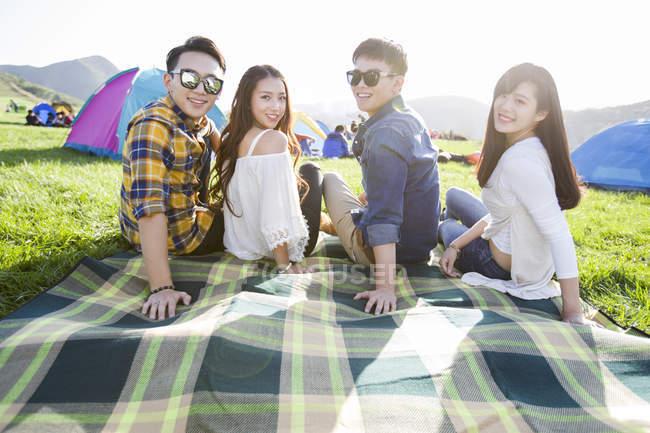 Amici cinesi seduti sulla coperta al festival musicale — Foto stock