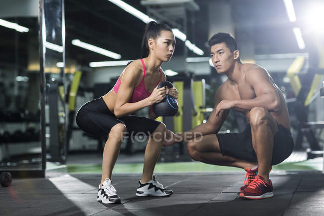 Donna cinese facendo sit up con kettlebell e trainer presso palestra — Foto stock