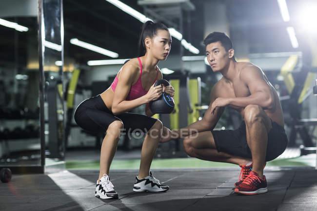 Chinesische Frau tun Sit up mit Kettlebell und Trainer im Fitness-Studio — Stockfoto