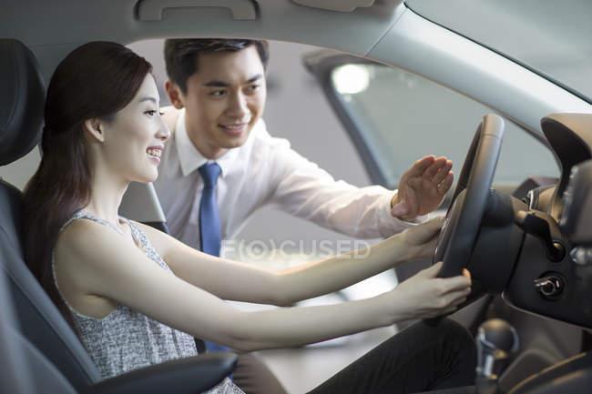 Voiture concessionnaire aider femme avec essai routier — Photo de stock