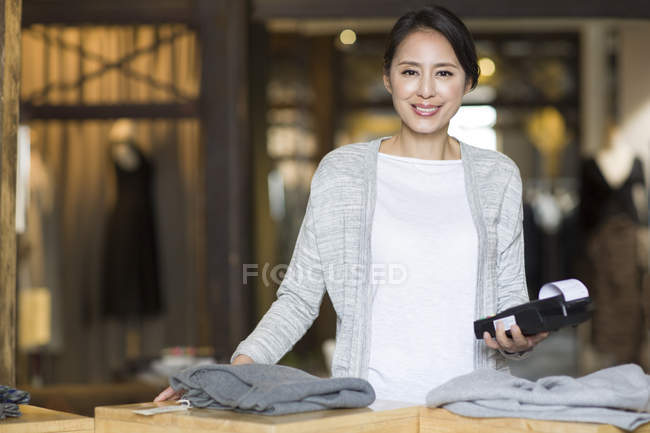 Chinese clothing store owner standing with credit card reader — Stock Photo