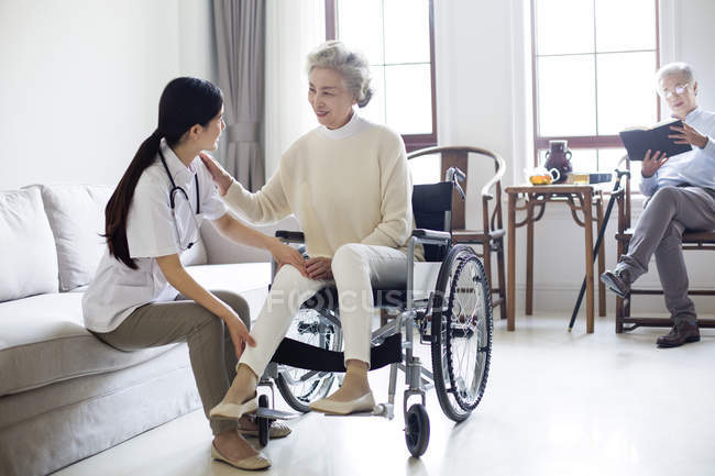 Китайская медсестра ухаживает за пожилой женщиной в инвалидной коляске, пока мужчина читает на заднем плане — стоковое фото