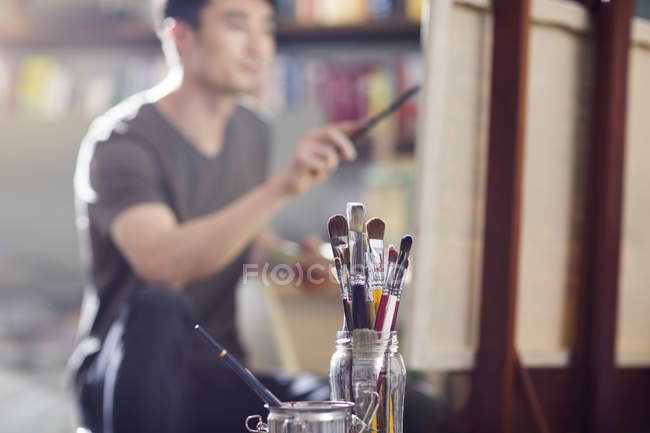 Paintbrushes in jar and male painter working in art studio — Stock Photo