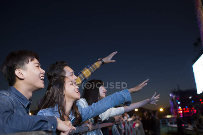 Chinese friends watching concert and singing at music festival — Stock Photo