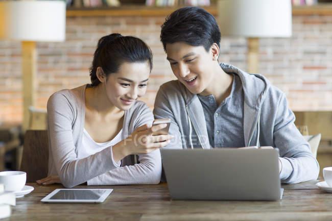 Coppia cinese utilizzando smartphone e laptop in caffè — Foto stock