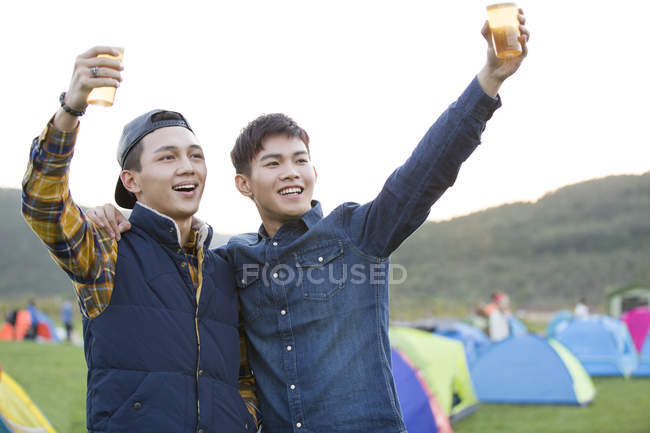 Chinese male friends drinking beer and cheering together — Stock Photo