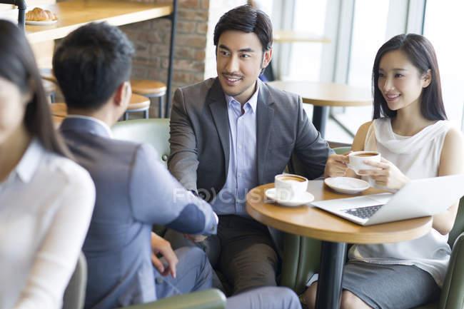 Азиатские бизнесмены пожимают руки во время встречи в кафе — стоковое фото