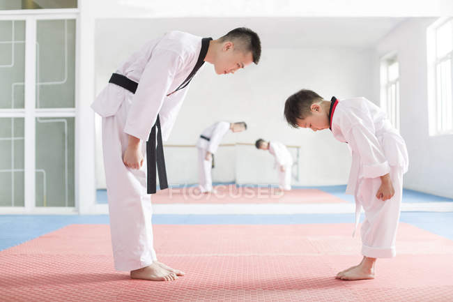 Chinese instructor and Taekwondo student bowing in exercise room — Stock Photo