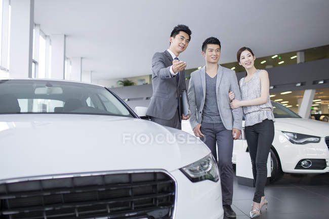 Car dealer showing cars to chinese couple in showroom — Stock Photo
