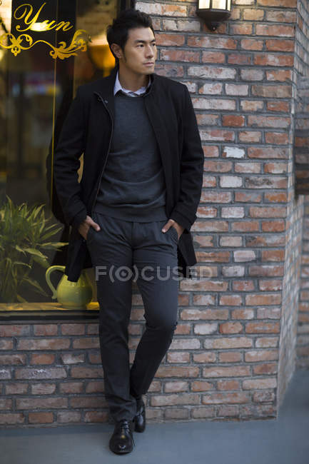 Asian man leaning to brick wall on urban street — Stock Photo