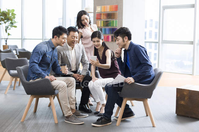 Chinese businesswoman showing smartphone to colleagues — Stock Photo