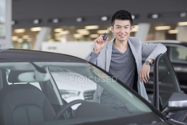 Uomo in possesso di chiavi per la nuova auto in showroom — Foto stock