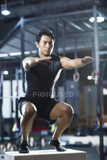 Chinese man doing box jump in crossfit gym — Stock Photo