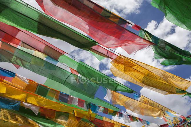 Bandiere di preghiera contro il cielo nuvoloso in Tibet, Cina — Foto stock