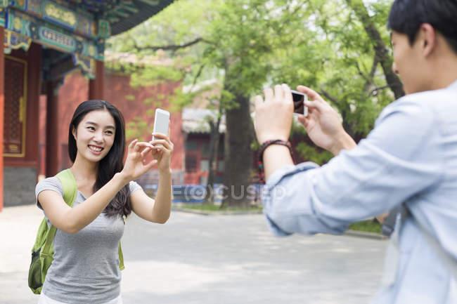 Coppia cinese scattare foto con smartphone nel Tempio di Lama — Foto stock