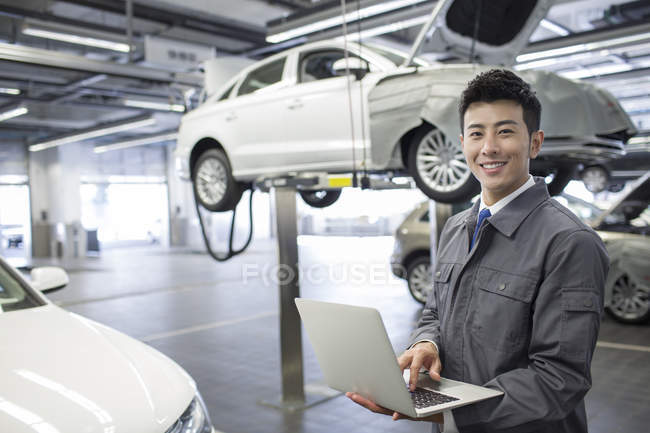 Chinese auto mechanic working with laptop in repair shop — Stock Photo
