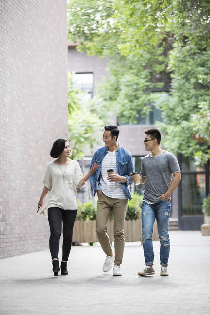 Chinese friends walking on street and holding coffee — Stock Photo