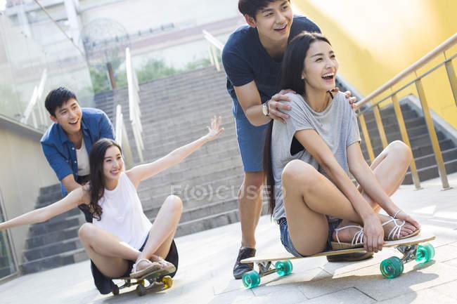 Chinese men pushing girlfriends on skateboards — Stock Photo