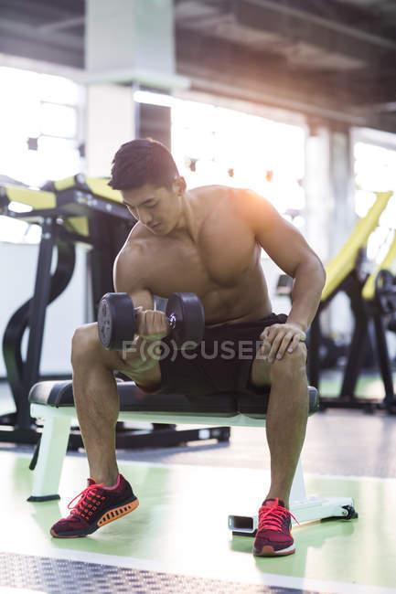 Chinese man lifting dumbbell at gym — Stock Photo