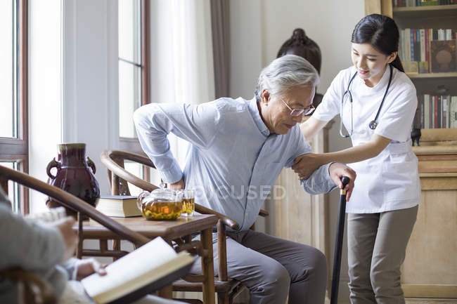 Chinese nursing assistant taking care of senior man in room with tea — Stock Photo