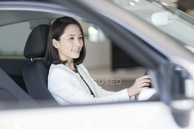 Chinese woman sitting in car on parking lot — Stock Photo
