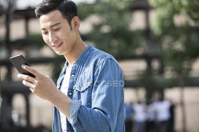 Uomo cinese utilizzando smartphone in città — Foto stock