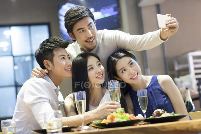 Asian friends taking selfie with smartphone while dinner in restaurant — Stock Photo
