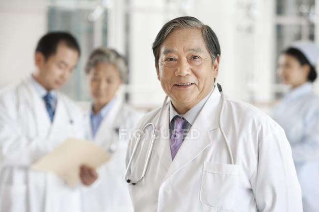 Chinês doutor em pé no hospital com os colegas no fundo — Fotografia de Stock