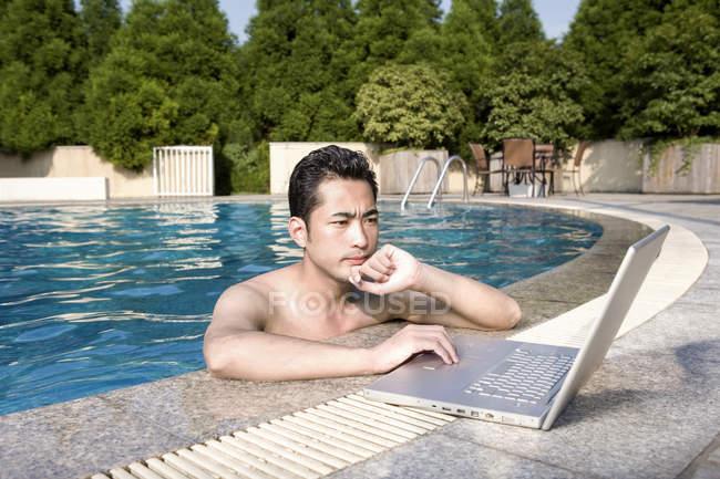 Chinese man using laptop at resort poolside — Stock Photo
