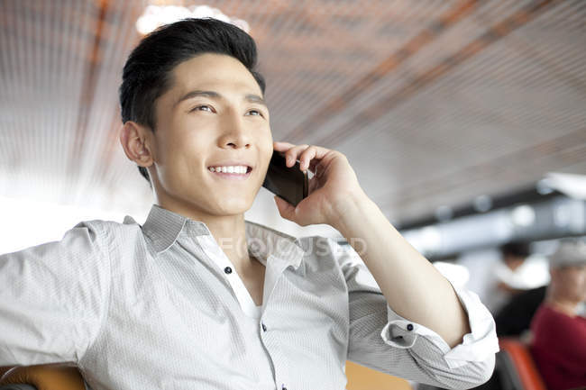 Chinese man talking on phone at airport building — Stock Photo