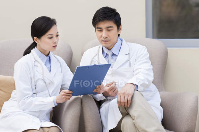 Chinese doctors sitting in armchairs and having discussion — Stock Photo
