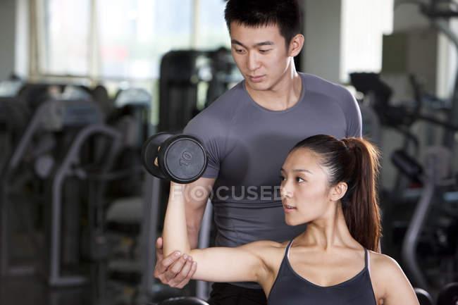 Тренер помогает китаянке поднять гантель — стоковое фото